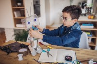 Little boy making robot toy of recycling material for school project