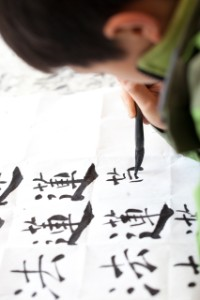 Chinese kid practice calligrapy on paper