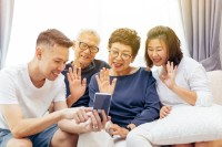 Extended family making a video call and waving at the caller. Asian multi generation family with senior and young couple together having happy time